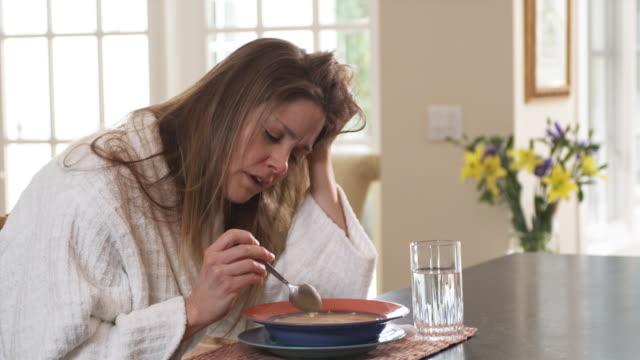 vídeos de stock, filmes e b-roll de ms woman coughing , sitting at dining table having bowl of soup, phoenix, arizona, usa - resfriado