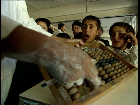 woman counts money and uses abacus as children watch chewing gum tajikistan - abakus bildbanksvideor och videomaterial från bakom kulisserna