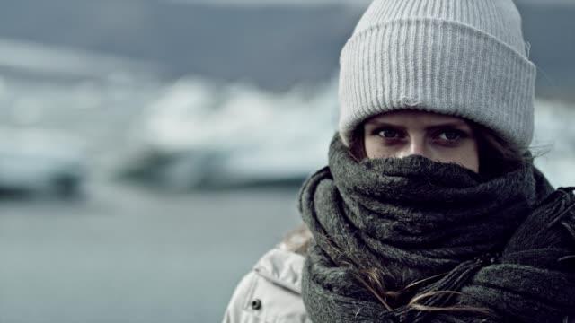 Femme recouverte du foulard fait froid près de glacier