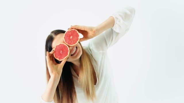 woman covering her eyes with two grapefruits - citrus fruit stock videos and b-roll footage
