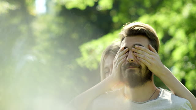 Woman covering mans eyes from behind at park