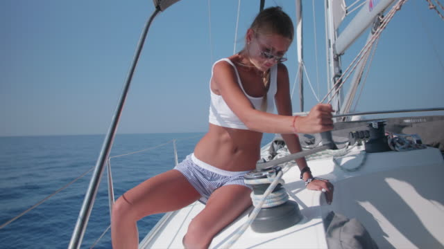 a woman cranking a winch with a handle while sailing a sailboat in the aegean sea of greece. - sailing stock videos & royalty-free footage