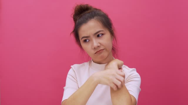 woman cratching her hand on isolated pink background 4k - mosquito stock videos & royalty-free footage