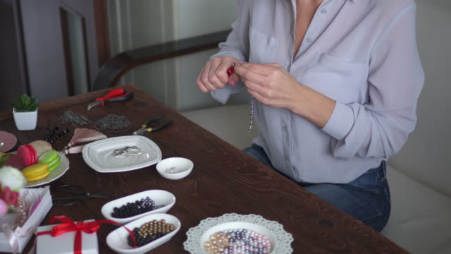 woman creating presents of beads at home - camicetta video stock e b–roll