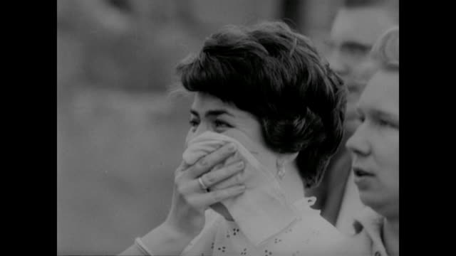 vídeos de stock e filmes b-roll de a woman cries as she waves to family across the berlin wall divide - 1961