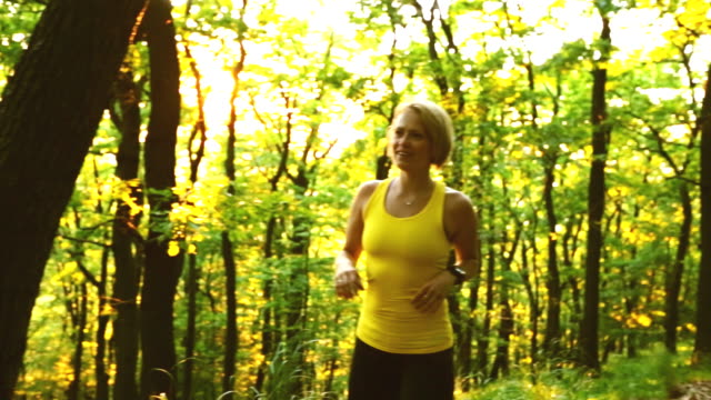 Woman cross country running in summer forest