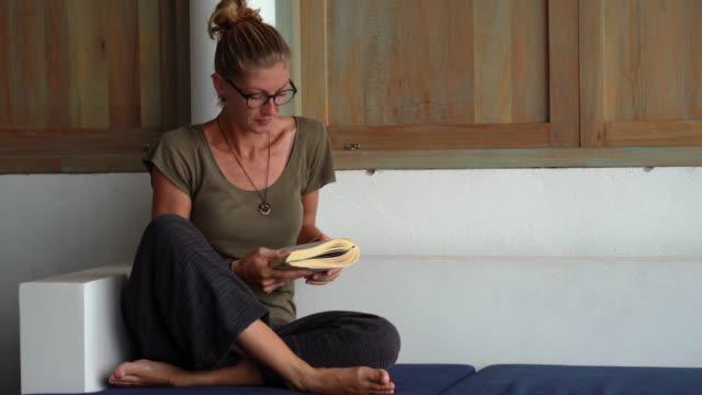 woman cross legged on sofa reading book - woman cross legged stock videos & royalty-free footage