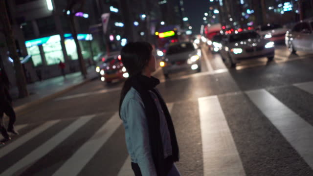 woman cross street in seoul at night, tracking shot - 横断する点の映像素材/bロール