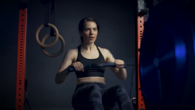 woman cross training at the garage gym on a rowing machine. - rowing machine stock videos & royalty-free footage