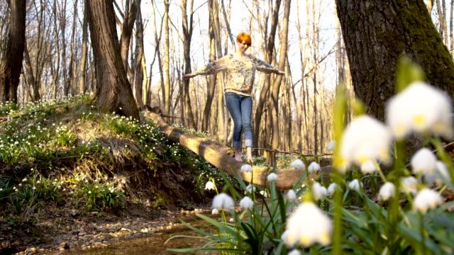 DS Frau überqueren eine creek über tree trunk