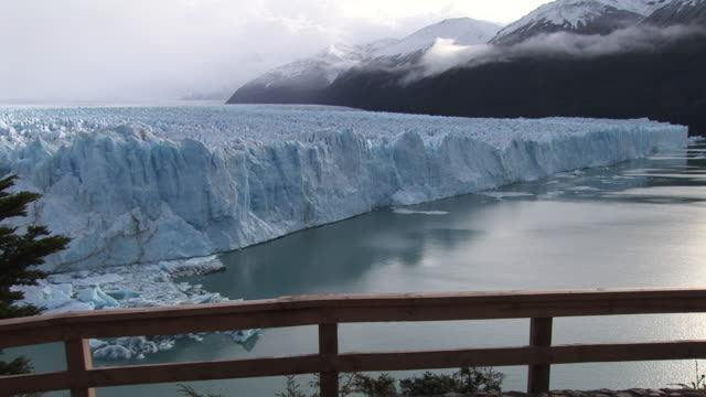 WS, Woman crossing bridge overlooking Perito Moreno Glacier, Los Glaciares National Park, Patagonia, Argentina
