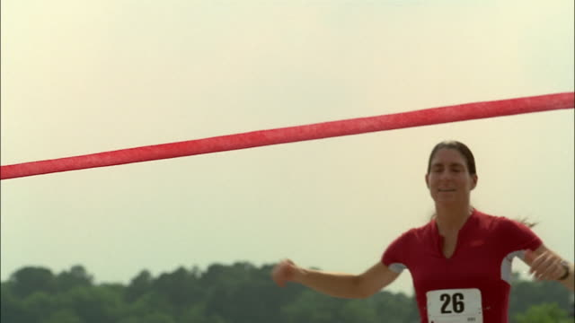 woman crossing finishing line at outdoor racing event / georgia - linea d'arrivo video stock e b–roll