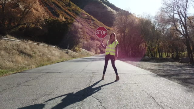 Woman crossing guard stopping traffic in canyon road