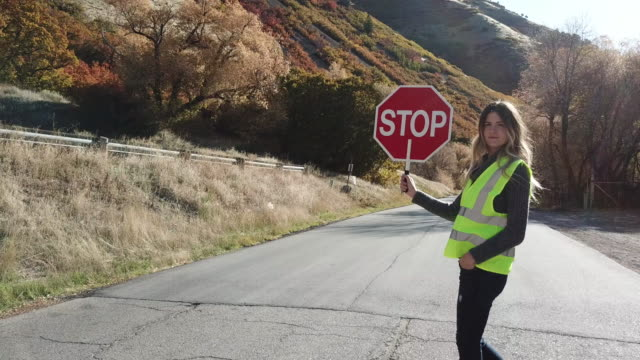 woman crossing guard stopping traffic in canyon road - stop sign stock videos and b-roll footage