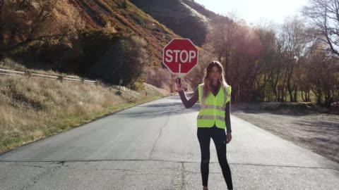 vidéos et rushes de femme brigadier scolaire s'arrêtant le trafic routier de canyon - signalisation