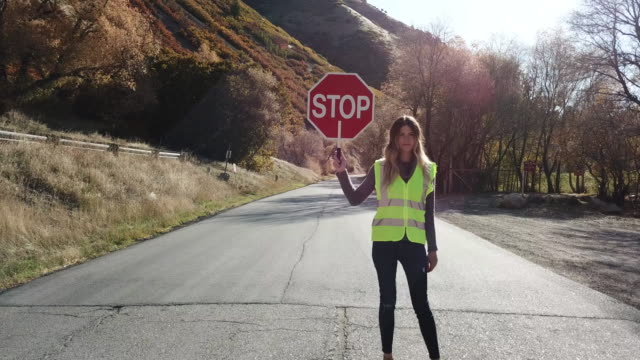 woman crossing guard stopping traffic in canyon road - stop sign stock videos & royalty-free footage