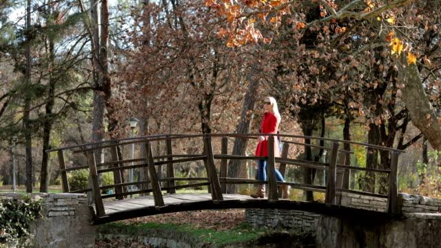 Woman crossing wodden bridge in park