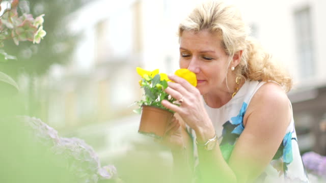 MS A Woman crouches down amongst the flowers to look closely and smell them
