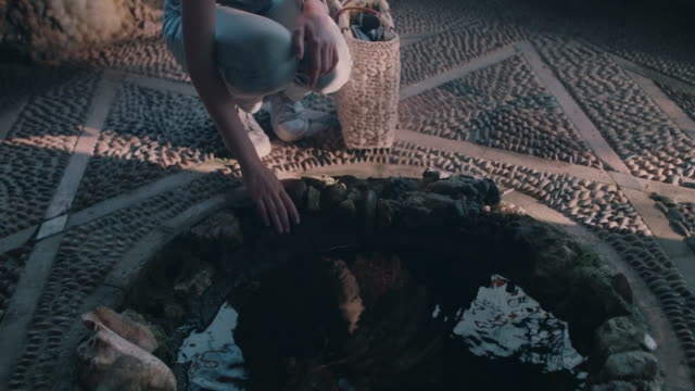 woman crouching next to pool/wishing well - wishing well stock videos & royalty-free footage
