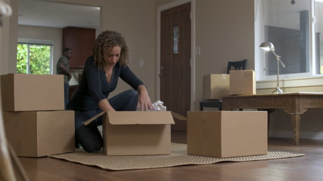 woman crouching on floor, unpacking crockery from boxes. - utensil stock videos & royalty-free footage