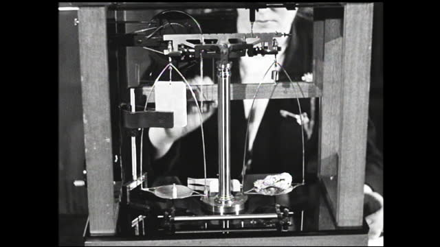 woman crumbles piece of foil and weighs it on small scale; worker working in the background; close up of scale being used - 1940 1949 stock videos & royalty-free footage