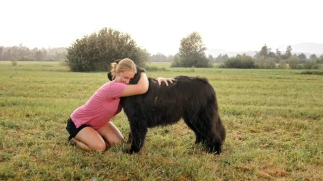 草原のニューファンドランド犬と寄り添う slo mo 女性 - tシャツ点の映像素材/bロール