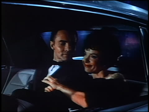 1961 woman cuddling with man in tuxedo in back of cadillac with projected scenery in background - cadillac stock videos & royalty-free footage