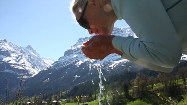 Woman cups hands to drink from mountain stream