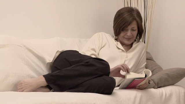 MS Woman curled up on sofa reading paperback book/ Rome, Italy
