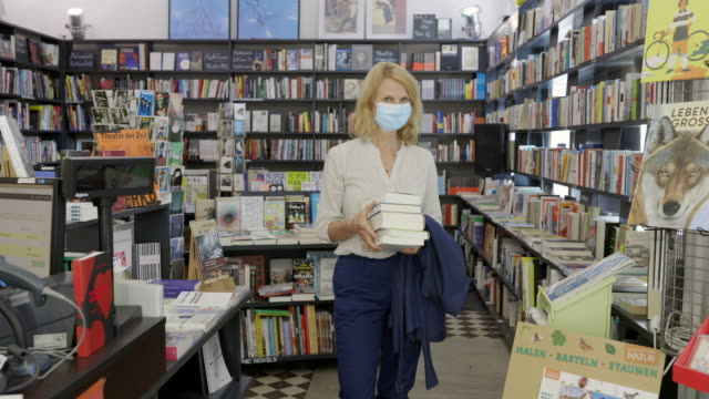 woman customer buying books in a bookstore during pandemic - book shop stock videos & royalty-free footage