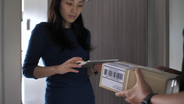 ドアで配達人から荷物を受け取る女性顧客 - 受ける点の映像素材/bロール