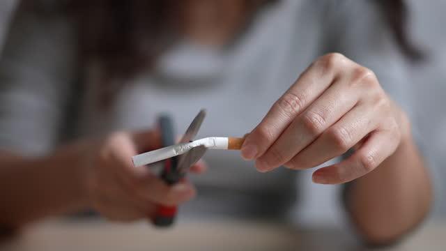 kvinna skär cigaretter med sax, sluta röka koncept, slow motion - släcka bildbanksvideor och videomaterial från bakom kulisserna