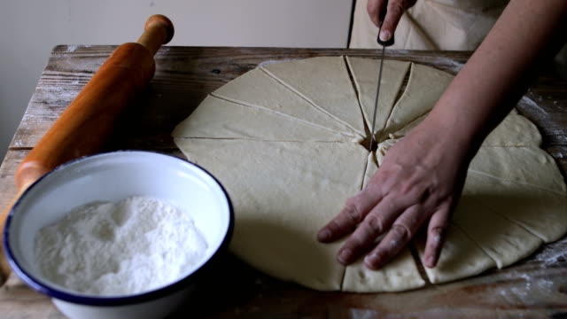 vídeos de stock e filmes b-roll de woman cuts dough on wooden table - corpo humano