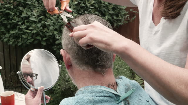 woman cuts hair of man while he looks on in mirror, back view. - diy stock videos & royalty-free footage
