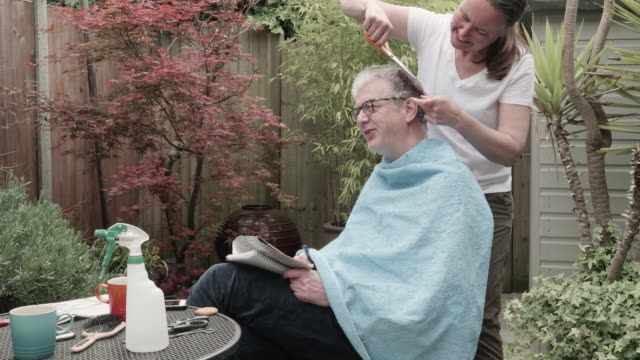 woman cuts man's hair in back garden, during lockdown. - hairstyle stock videos & royalty-free footage