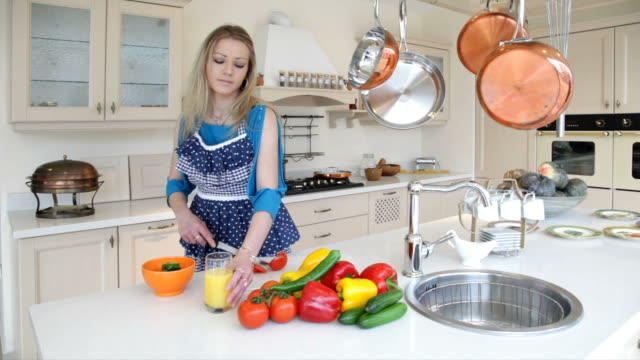 woman cuts vegetables and drinks orange juice in kitchen - stereotypically working class stock videos and b-roll footage