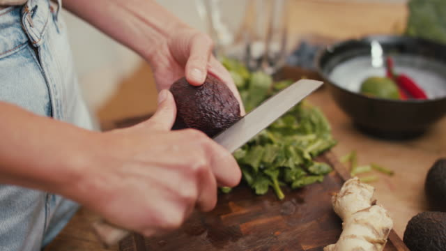 woman cutting avocado in kitchen at home - chopping board stock videos & royalty-free footage