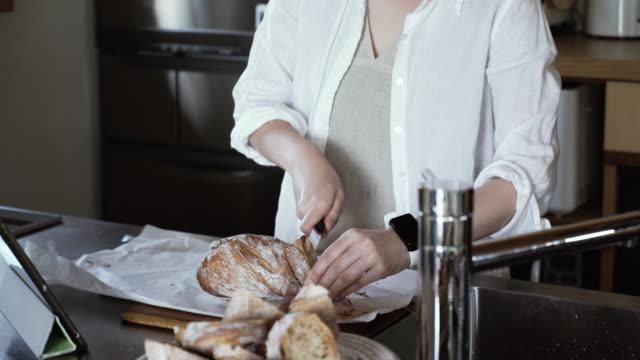 台所で女性切断バゲット - 家事点の映像素材/bロール