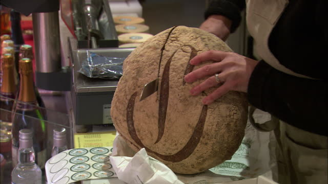 cu zo ms woman cutting bread in delicatessen / beaune, burgundy, france - peasant bread stock videos and b-roll footage