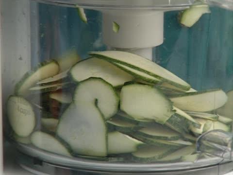 Woman cutting cucumber in blender