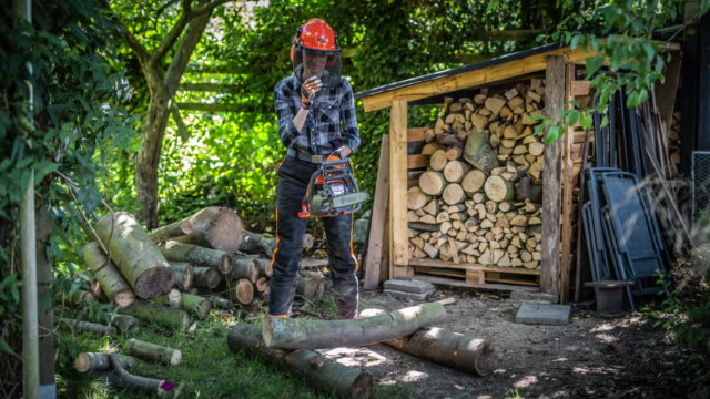 woman cutting firewood with a chainsaw - firewood stock videos & royalty-free footage