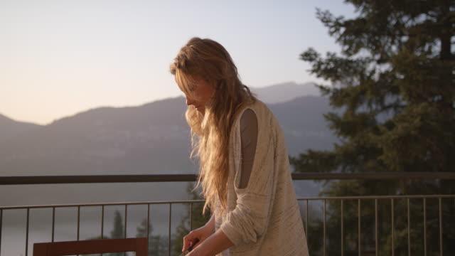 frau schneidet frisches essen auf balkon mit blick auf berge und see bei sonnenuntergang - geländer stock-videos und b-roll-filmmaterial