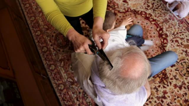 stockvideo's en b-roll-footage met vrouw die het haar van haar echtgenoot bij woonkamer tijdens isolatieperiode snijdt - in een handdoek gewikkeld