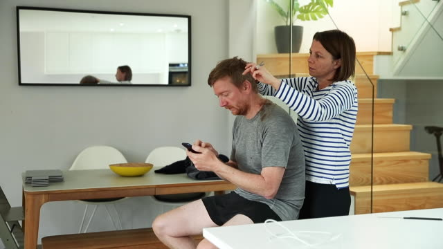 woman cutting her partner's hair at home - cutting hair stock videos & royalty-free footage