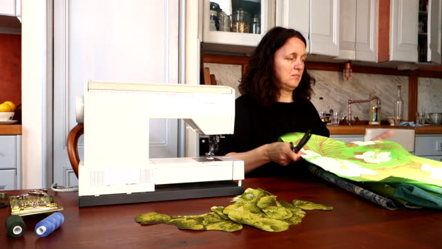 woman cutting leaf shapes from printed fabric - tapestry stock videos & royalty-free footage