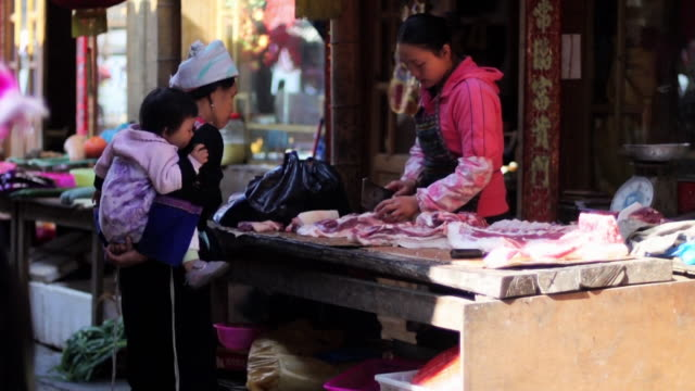 Woman cutting meat at street