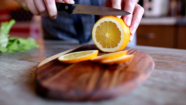 Woman cutting orange in her kitchen