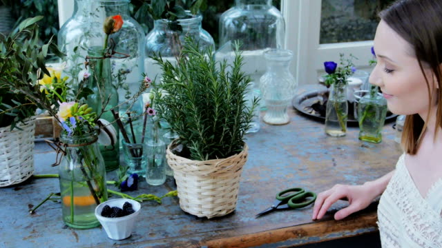 Woman cutting plant twig and smelling it