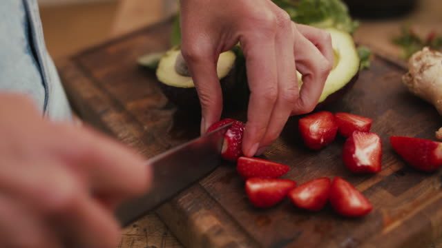 woman cutting strawberries on wooden cutting board in kitchen at home - cutting stock videos & royalty-free footage