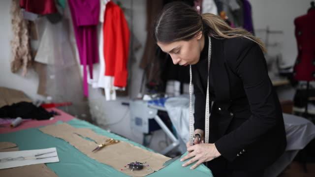 vídeos y material grabado en eventos de stock de mujer cortando la tela - tijeras